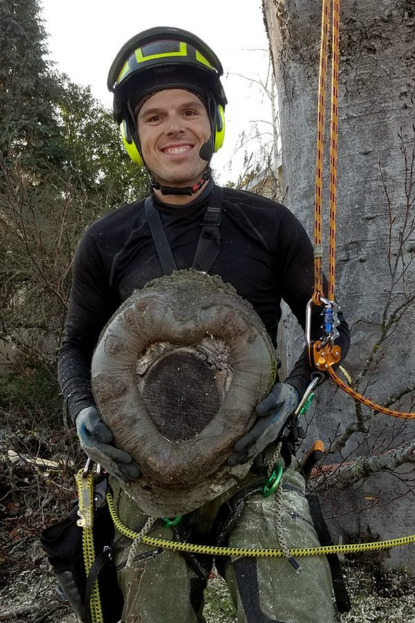 Tree Service Professional Jacob holding heart shaped stump